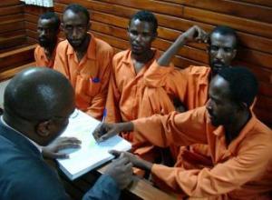 El abogado Francis Kadima, de espaldas, habla con un grupo de piratas en el juzgado de Mombasa.- AFP