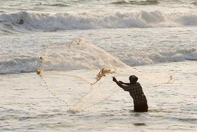 Un pescador lanza la red en la costa del Índico. -Markus Spring