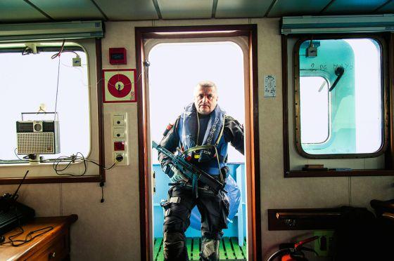 Un agente de Vigilancia Aduanera se presenta en el puente de mando del buque de operaciones especiales Fulmar, armado con subfusil de asalto, antes de llevar a cabo una operación en alta mar. / GIANFRANCO TRIPODO
