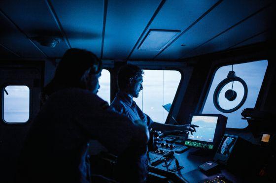 Marinos del Servicio de Vigilancia Aduanera observan la evolución de embarcaciones circundantes en la pantalla de una cámara térmica, situada en el puente de mando del buque de operaciones especiales Fulmar. / GIANFRANCO TRIPODO