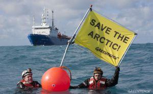 """Dos activistas de Greenpeace ante el buque ruso de prospección Académico Lazarev, en el mar de Barents, con la pancarta """"Salvar el Ártico"""". / GREENPEACE"""
