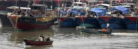Pescadores esperan en el puerto de Hainan el paso del tifón Wutip. / Reuters
