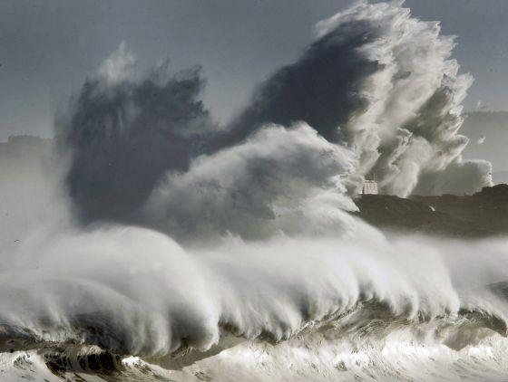 Una gran ola rompe frente a la isla de Mouro, en la bocana del puerto de Santander, el pasado domingo durante el temporal. / ESTEBAN COBO / EFE