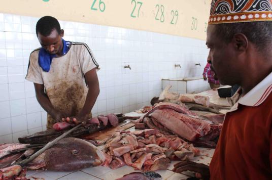 Un vendedor corta en filetes un pez para un cliente en la lonja de Mogadiscio (A. Pampliega)
