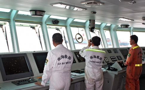 Nanhai Rescue Bureau (NRB) rescuers searching for survivors in the water after the Marshall Islands-registered MOL Motivator (in the background) collided with a Chinese cargo ship, the Zhong Xing 2, off Hong Kong waters. Photo: AFP
