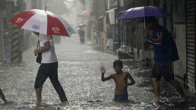 Filipinos enfrentan las lluvias de un tifón en Manila.