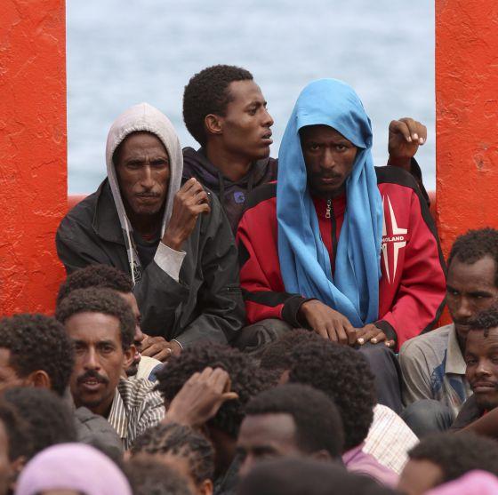 Un grupo de inmigrantes a bordo de un barco de la Armada italiana frente a Augusta en junio. / a. parinello (reuters)