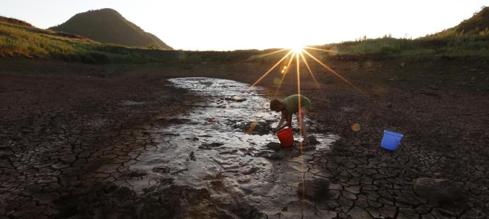 Un hombre recoge agua de un pozo casi seco en Xinchang, China. (Reuters