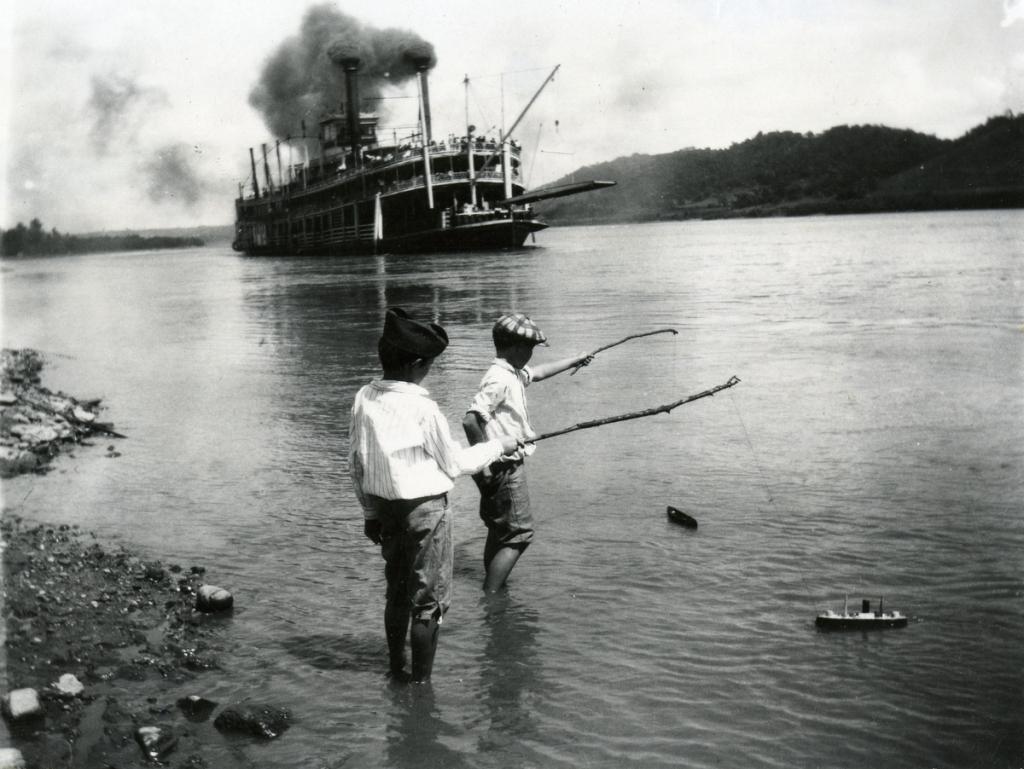 Niños juegan con sus barcos de juguete mientras uno de vapor atraviesa el río en Rising Sun, Indiana, en 1919. (Foto de Felix Koch/Cincinnati Museum Center/Getty Images)