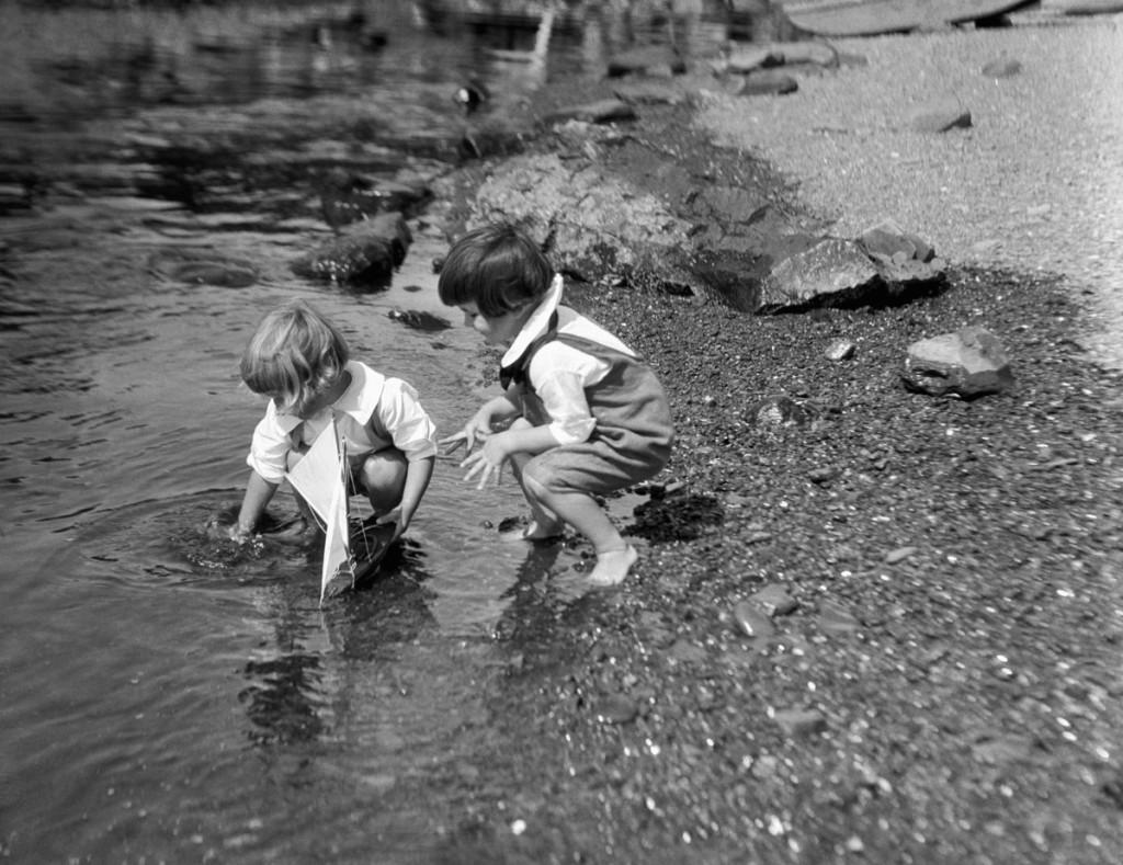 Dos niños juegan alrededor de 1930 en la orilla del río con un velero de juguete. (Foto de H. Armstrong Roberts/Retrofile/Getty Images)