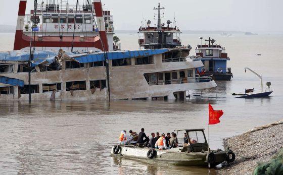 Trabajadores sobre el barco naufragado tras lograr enderezarlo. / AFP