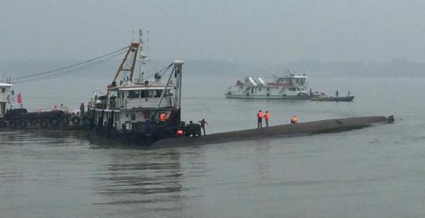 Una grúa intenta voltear al barco hundido en el río Yangtsé. /REUTERS