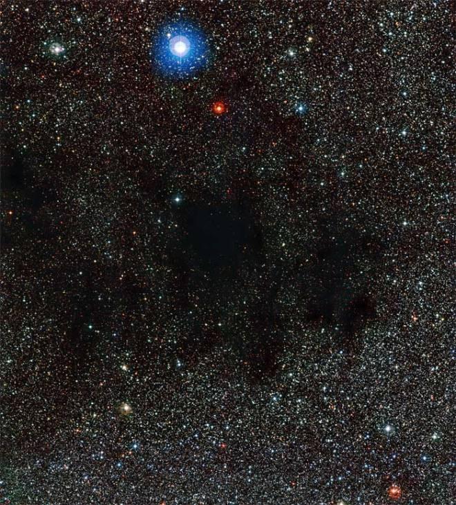 Esta imagen de la cámara Wide Field Imager (instalada en el Telescopio MPG/ESO de 2,2 metros), muestra parte de la enorme nube de polvo y gas conocida como la nebulosa Saco de Carbón. El polvo de esta nebulosa absorbe y dispersa la luz de las estrellas del fondo. Crédito: ESO